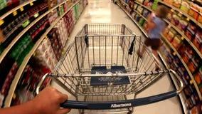 Verkeer op de supermarkt met een mand voor voedsel stock video