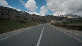 Verkeer op de vlakke weg aan de bergen in de lente stock footage