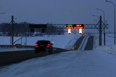 Verkeer op een donkere weg in de winter Stock Foto
