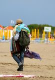 Verkeerde Venter die met stoffen en kleding op het strand lopen Stock Fotografie