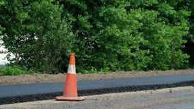 Verkeerskegel op weg De wegenbouwwerken, wegreparatie Op de weg is er vers die asfalt aan één kant van wordt gelegd stock video