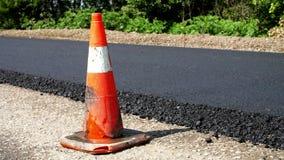 Verkeerskegel op weg De wegenbouwwerken, wegreparatie Op de weg is er vers die asfalt aan één kant van wordt gelegd stock videobeelden
