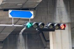 Verkeerslicht de lichten rode pijlen om de auto tegen te houden en groene pijlen zijn om met de raad van straatnamen te gaan Royalty-vrije Stock Afbeelding