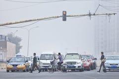 Verkeerslichten met auto's en voetgangers in smog behandeld Peking, China stock afbeeldingen