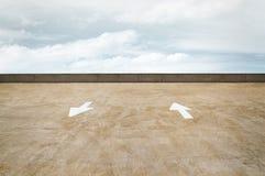Verkeerspijlen op een Dak van de Parkerengarage met een Bewolkte Hemel Royalty-vrije Stock Foto