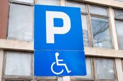 Verkeersteken die op een parkerenplaats en op een plaats voor mensen gehandicapt met auto's wijzen stock afbeelding