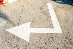 Verkeersteken die op Wit pijlteken op de straat, Richting voor verkeersveiligheid wijzen witte pijlen die richtingen op grijs ric stock foto's