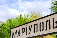 Verkeersteken met de inschrijving in Oekraïense Mariupol, stad van het gebied van Donetsk, die door kogels wordt geslagen, Oekraï stock fotografie