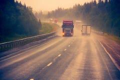Verkehr auf nasser schlechter Landstraße Lizenzfreies Stockfoto