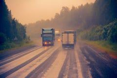 Verkehr auf nasser schlechter Landstraße Lizenzfreie Stockfotografie