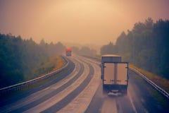 Verkehr auf nasser schlechter Landstraße Lizenzfreie Stockfotos
