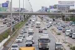 Verkehr bewegt sich langsam entlang eine verkehrsreiche Straße in Bangkok Stockfotos