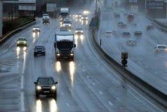 Verkehr an der D?mmerung im Regen lizenzfreie stockbilder