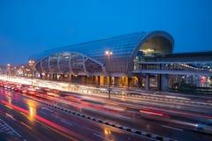 Verkehr mit heller Spur nahe bei dem Bahnhof während der blauen Stunde nach dem Regen stockbild