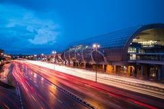 Verkehr mit heller Spur nahe bei dem Bahnhof während der blauen Stunde nach dem Regen stockfotografie