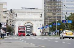 Verkehr und Doubledeckerbus vor mazedonischem Tor in Skopje, das eins der vielen Monumente ist stockbild