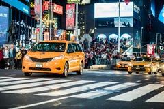 Verkehr und gelbe hybride Fahrerhäuser im Times Square nachts, Manhatt lizenzfreie stockfotos