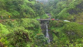Verkehr verlangsamt an einer schmalen Brücke über einem Wasserfall auf Maui stockfotos