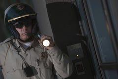 Verkehrs-Bulle, die mit Taschenlampe nachts nachforscht Stockfoto