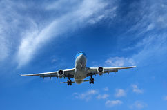 Verkehrsflugzeug unter wispy Wolken Lizenzfreie Stockbilder