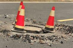 Verkehrskegel und Einsteigelochabdeckung   Stockfoto