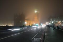 Verkehrsreiche Straße mit Verkehr und Fußgänger nachts nebeliges in London stockbild