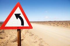 Verkehrsschild, das linke Kurve in der Straße anzeigt Stockbild