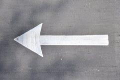 Verkehrsschild gehen nach links auf den Asphalt, der mit weißer Farbe gemalt wird Stockfotos