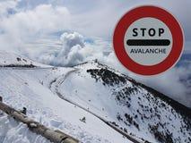 Verkehrsschild Halt Warnen der Gefahr in den Bergen Lawinenrückzug Gefahr auf dem Schnee-mit einer Kappe bedeckten Berg übersteig Lizenzfreie Stockfotos