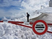 Verkehrsschild Halt Warnen der Gefahr in den Bergen Lawinenrückzug Gefahr auf dem Schnee-mit einer Kappe bedeckten Berg übersteig Lizenzfreie Stockfotografie