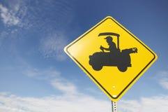 Verkehrsschild mit älterem antreibendem Golfwagen. Stockfotografie
