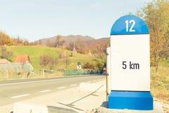 Verkehrsschild oder Meilenstein, die 5 Kilometer zum Bestimmungsort zeigen Stockfotografie