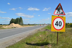 Verkehrsschilder Straßenarbeiten und Beschränkung der Höchstgeschwindigkeit von 40 Kilometern auf einem Straßenstraßenrand Lizenzfreie Stockfotografie