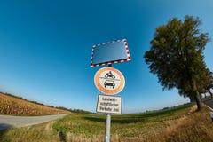 Verkehrsschilder und Spiegel an der Land-Straße mit tiefem blauem Himmel Lizenzfreie Stockfotografie