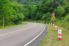 Verkehrsschilder und verbiegende Straße zur Spitze eines Berges mit Gre Stockbilder