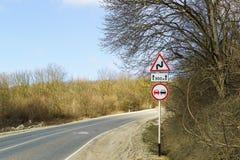 Verkehrsschilder verbieten auf dem Überholen an einer scharfen Drehung der Landstraße Stockfotografie