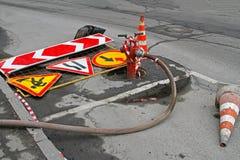 Verkehrsschilder, Verkehrskegel und roter Hydrant mit Schlauch Stockfoto