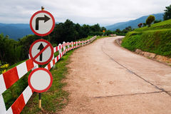 Verkehrszeichen auf Kurvenstraße Stockbild