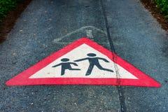Verkehrszeichen Aufmerksamkeitskinder, die auf dem Boden einer Straße spielen Lizenzfreies Stockfoto