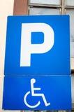Verkehrszeichen, das einen Parkplatz und einen Platz für Leute mit Unfähigkeit mit Autos anzeigt Lizenzfreies Stockfoto