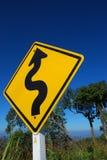 Verkehrszeichen der kurvenreichen Straße mit klarem blauem Himmel Lizenzfreie Stockfotos