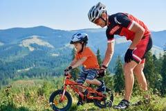 Verkhovyna, Ukraine - 19 août 2017 : Le papa fier dans l'équipement de cycliste aide son fils mignon préscolaire à monter un vélo Photographie stock libre de droits