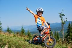 Verkhovyna, Ukraine - August 19, 2017: boy in helmet and summer clothes points at something up riding child bicycle. Verkhovyna, Ukraine - August 19, 2017: Small Royalty Free Stock Images