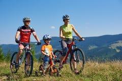 Verkhovyna, Ukraine - 19. August 2017: touristische Familie, Mutter, Vati und Junge mit Berg fährt auf Gebirgsgrasartiges Tal rad lizenzfreie stockfotos