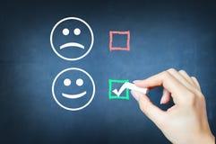 Verkies gelukkig te zijn met tik tegen smileygezicht op bord royalty-vrije stock afbeelding