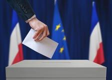 Verkiezing in Frankrijk De kiezer houdt envelop boven stemstemming in hand royalty-vrije stock afbeelding