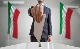 Verkiezing of referendum in Italië De kiezer houdt envelop boven stemming in hand Italiaanse vlaggen op achtergrond stock foto