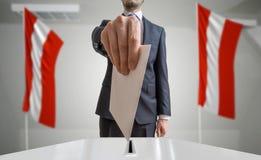 Verkiezing of referendum in Oostenrijk De kiezer houdt envelop boven stemming in hand Oostenrijkse vlaggen op achtergrond stock foto's