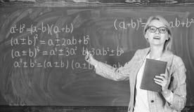 Verklaart de leraars slimme vrouw met boek onderwerp dichtbij bord De schoolleraar verklaart goed dingen en maakt onderworpen stock foto