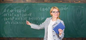 Verklaart de leraars slimme vrouw met boek onderwerp dichtbij bord De schoolleraar verklaart goed dingen en maakt onderworpen royalty-vrije stock fotografie